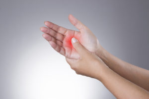 pain in the joints of the hands. carpal tunnel syndrome. pain in the human body on a gray background with red dot